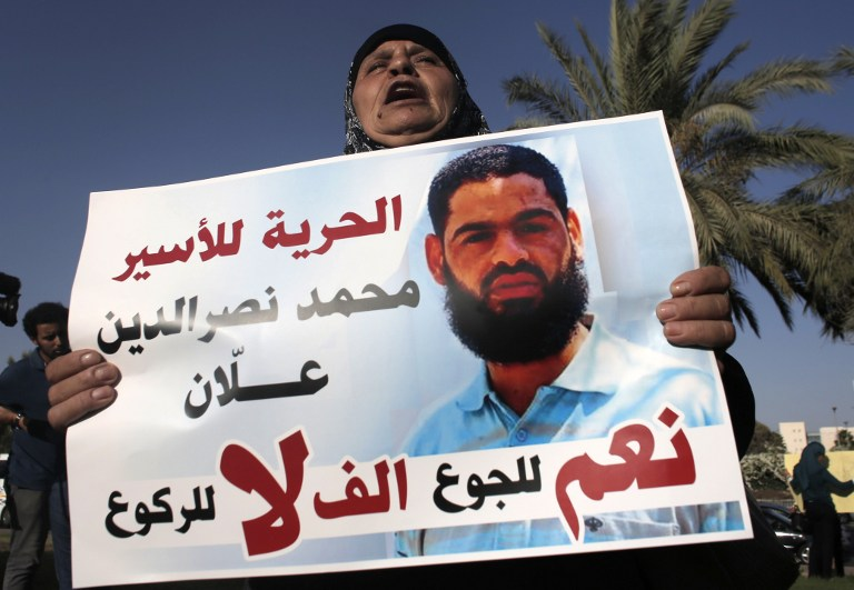 Maazouze, the mother of Mohammed Allaan, a Palestinian prisoner who is on a long-term hunger strike, holds a portrait of her son during a rally calling for his release in the southern Israeli city of Beersheba on August 9, 2015. (AFP/Ahmad Gharabli)