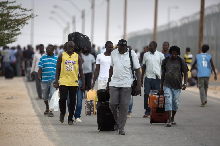 African illegal migrants carry their belongings following their release from the Holot Detention Center in Israel's Negev desert, on August 25, 2015. (AFP PHOTO/MENAHEM KAHANA)