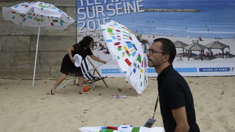 "A woman sets up a parasol during the ""Tel-Aviv sur Seine"" beach attraction as part of the  14th edition of Paris Plages (Paris Beaches) in central Paris, on August 13, 2015. Paris was to deploy some 500 police along the River Seine on August 13, at the start of a controversial beach attraction dedicated to Tel Aviv.  (Kenzo Tribouillard/AFP)"