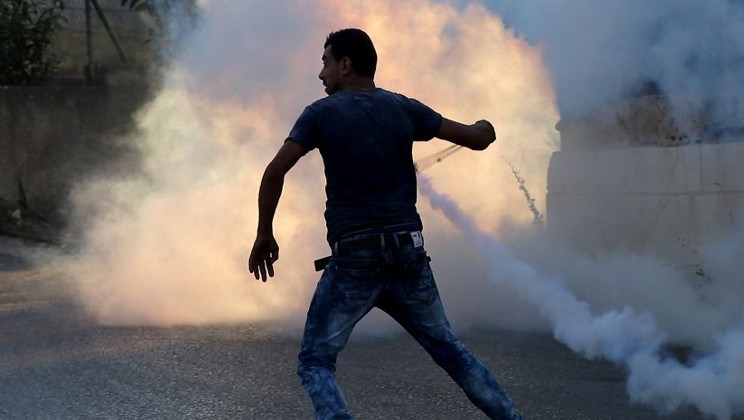 A Palestinian protester uses a slingshot during clashes with Israeli security forces on July 31, 2015 nearby the Jalazoun Palestinian refugee camp and the Jewish settlement of Beit El, north of Ramallah in the West Bank. (AFP/ ABBAS MOMANI)