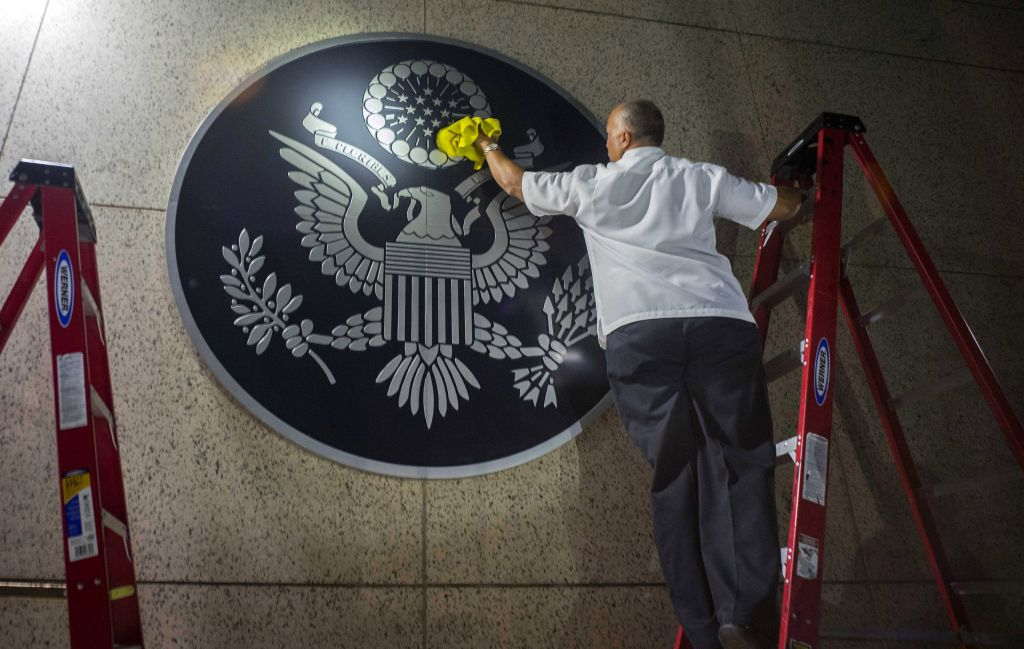 A worker wipes a representation of the The Great Seal of the United States at the newly opened US Embassy in Havana, Cuba, Friday, Aug. 14, 2015. (AP Photo/Ramon Espinosa)