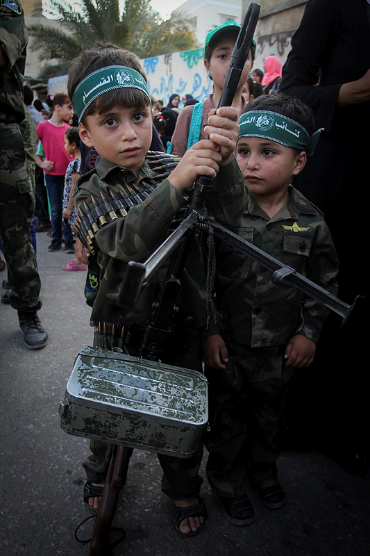 A Palestinian boy holds his father's weapon during a graduation ceremony as part of a military-style summer camp organised by Hamas on August 5, 2015, in Khan Yunis, in the southern Gaza Strip. (Abed Rahim Khatib/ Flash90)