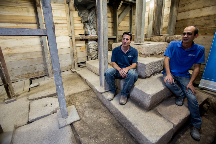 Israel Antiquity Authority archaeologists sit on a stair structure found on a street ascending the Siloam Pool to Jerusalem's Old City, on August 31, 2015. (Yonatan Sindel/Flash90)