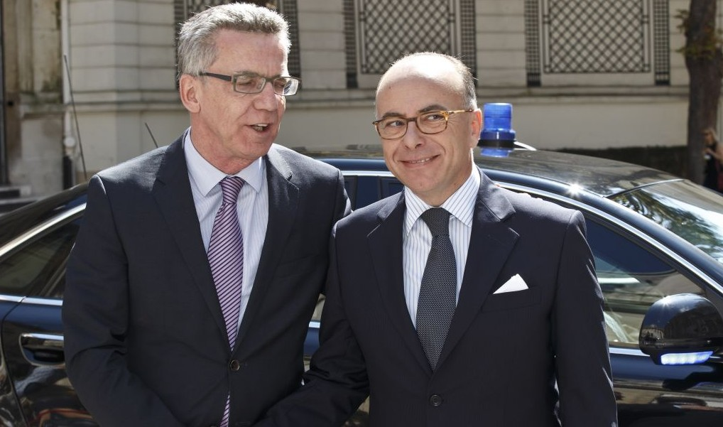 German Interior Minister Thomas de Maiziere, left, is welcomed by French counterpart Bernard Cazeneuve, right, for an emergency meeting in Paris, France, Saturday, Aug. 29, 2015. (AP Photo/Michel Euler)
