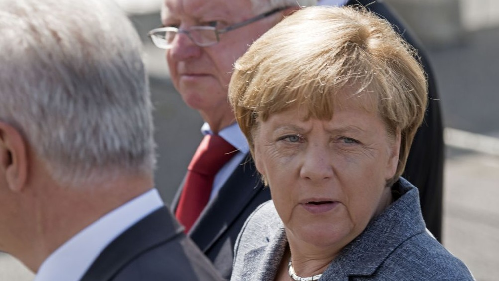 germany s merkel vows to crack down on refugee attacks