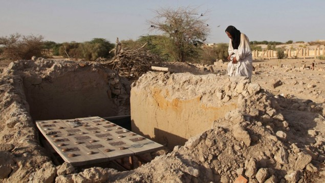 In this Friday, April 4, 2014 file photo, Mohamed Maouloud Ould Mohamed, a mausoleum caretaker, prays at a damaged tomb in Timbuktu, Mali. (AP Photo/Baba Ahmed, File)