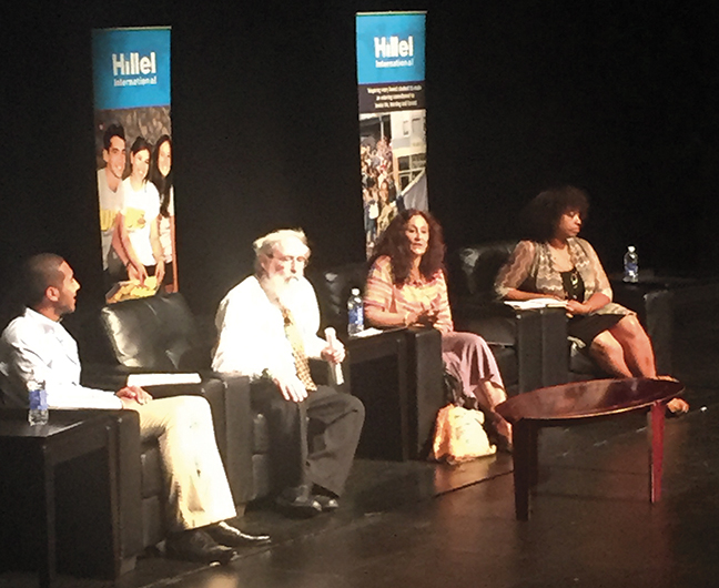 At the Hillel conference, a student moderator, at left, sits on stage with speakers Rabbi Saul Berman, Rabbi Susan Talve, and Yavilah McCoy.