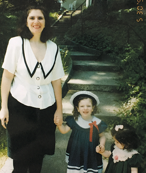 Esther Chalom holds her small daughter Talia Mizikovsky's hand, and Talia holds on to her younger sister, Anabelle.