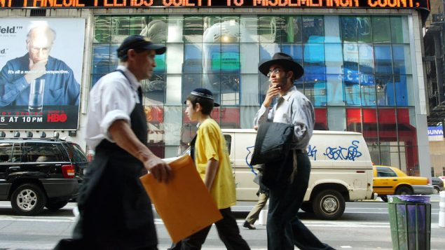 Jewish pedestrians walking in Manhattan's Times Square: New York has the biggest Jewish population in the U.S. JTA