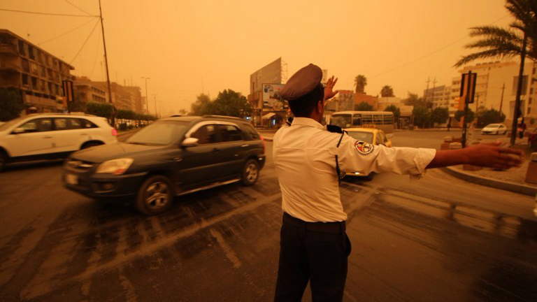 An Iraqi policeman organizes traffic on a street in the capital Baghdad during a sandstorm on September 1, 2015. (AFP Photo/Haidar Mohammed Ali)
