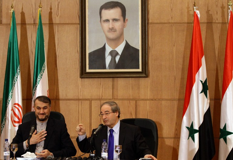 Hussein Amir-Abdollahian (L), Iran's deputy Foreign Minister for Arab-African Affairs and Syrian deputy Foreign Minister Faisal Moqdad (R) sit under a portrait of Syrian President Bashar al-Assad during a joint press conference in the Syrian capital, Damascus, on September 3, 2015. (AFP/LOUAI BESHARA)