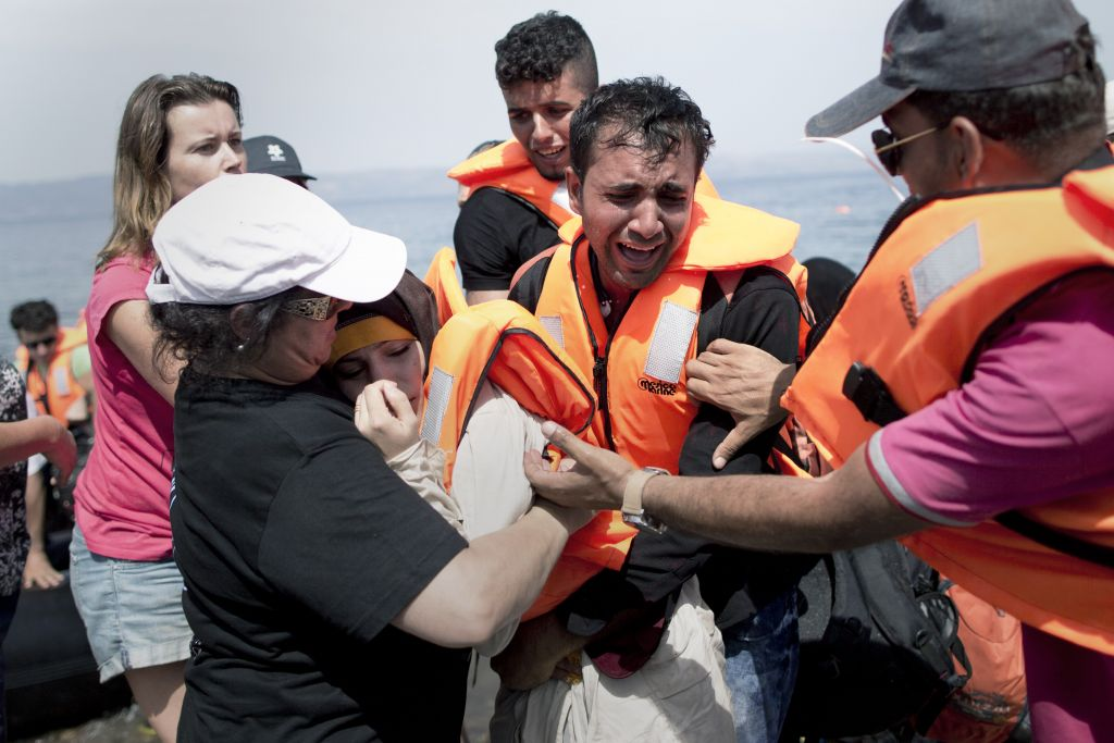 A volunteer helps a Syrian women that collapsed as her husband cries as they arrive aboard a dinghy after crossing from Turkey, on the island of Lesbos, Greece, Monday, September 7, 2015. (Petros Giannakouris/AP)
