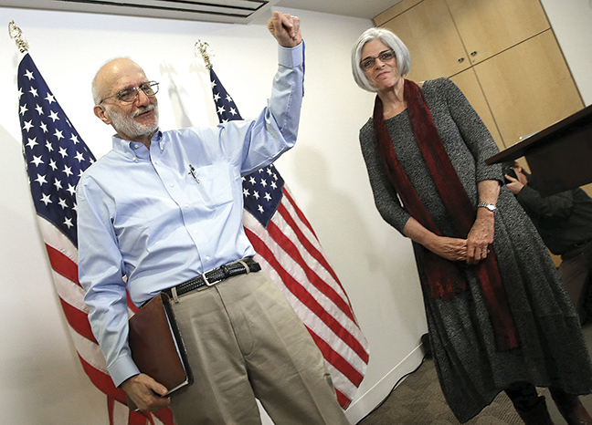 Alan Gross, freed from a Cuban prison earlier in the day, waves after concluding his remarks with his wife, Judy, at a news conference in Washington shortly after arriving in the United States on December 17, 2014. (Win McNamee/Getty Images)