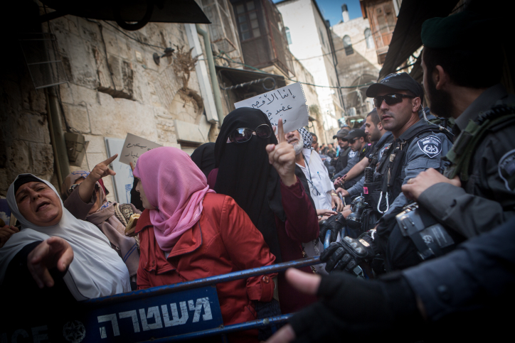 Palestinian Muslim women from the Murabitun group shout slogans and hold the Koran during a protest against Israel policemen preventing them from entering the Temple Mount compound in Jerusalem's Old City on September 17, 2015. (Miriam Alster/Flash90 )