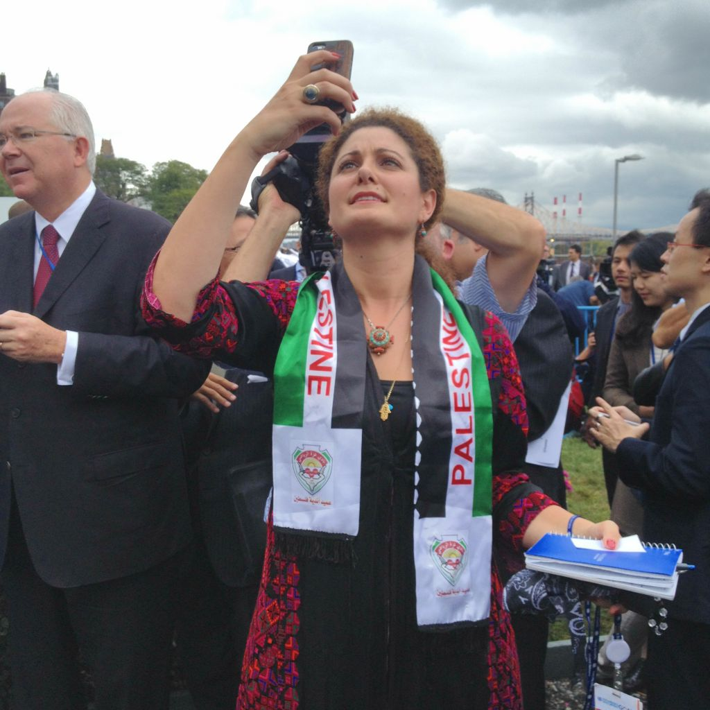 A woman takes a photo as the Palestinian flag is raised outside UN Headquarters in New York, September 30, 2015 (Raphael Ahren)