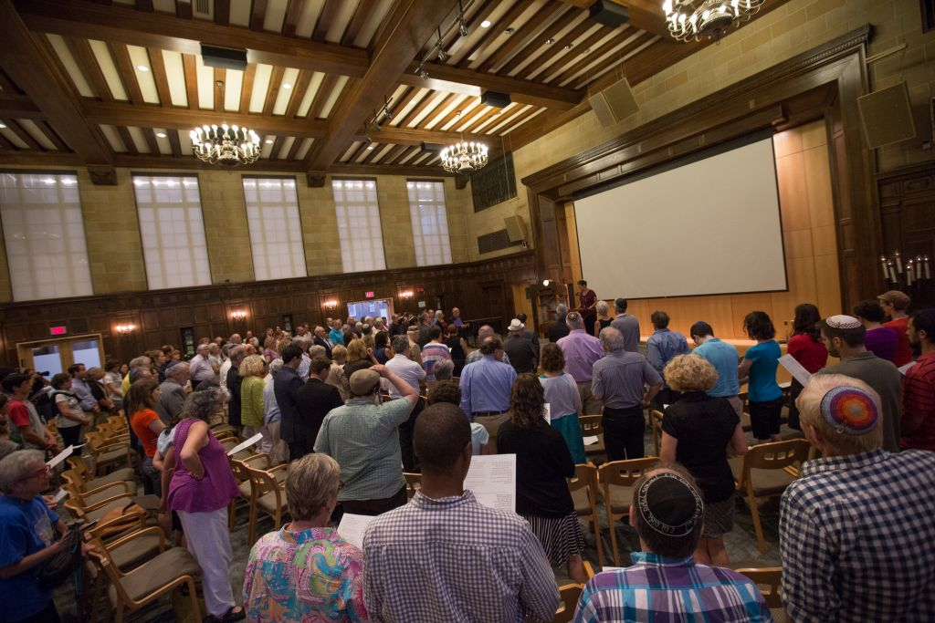 Gathered at Boston's Temple Israel on September 9, 2015, up to 200 community members held a Memorial and Solidarity Gathering for victims of violent Jewish extremism in Israel during the past summer. At the gathering's conclusion, participants read the Mourner's Kaddish prayer. (Elan Kawesch/The Times of Israel)