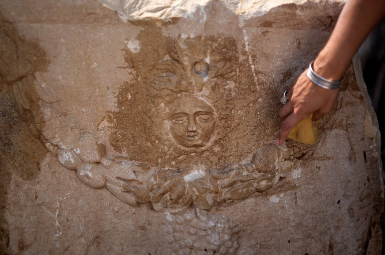 A member of the Israel Antiquities Authority (IAA) cleans the head of the monstrous mythological female figure Medusa which includes images of the venemous snakes that she was said to have as hair on a unique Roman-era sarcophagus adorned with the carving of a young man at a warehouse in Bet Shemesh on September 3, 2015. (AFP PHOTO/MENAHEM KAHANA)