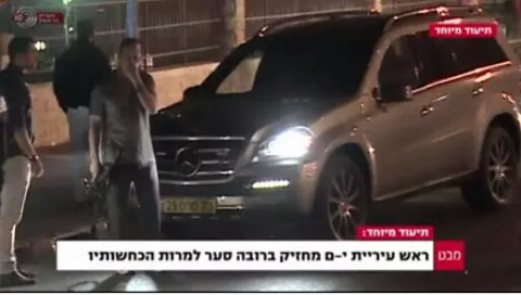 "A screen capture from Channel 1 shows Mayor Nir Barkat with a gun. The caption says ""Jerusalem mayor carries unlicensed assault rifle, despite his denials."" (Screen capture Channel 1)"