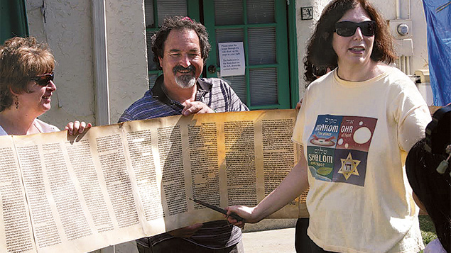 Rabbi Orenstein reads Torah surrounded by members of her California shul, Makom Ohr Shalom.