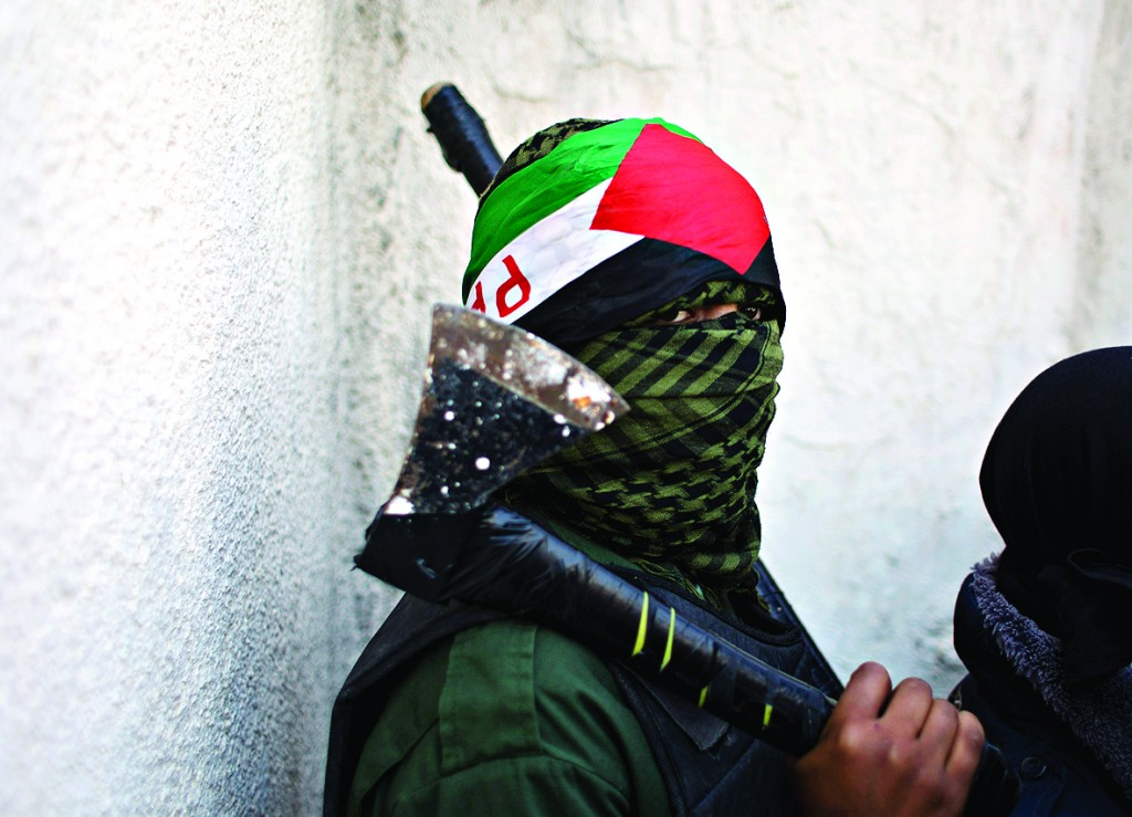 A masked Palestinian youth carries an axe in the Palestinian West Bank refugee camp of Jalazoun, Ramallah,    (AP Photo/Nasser Nasser)