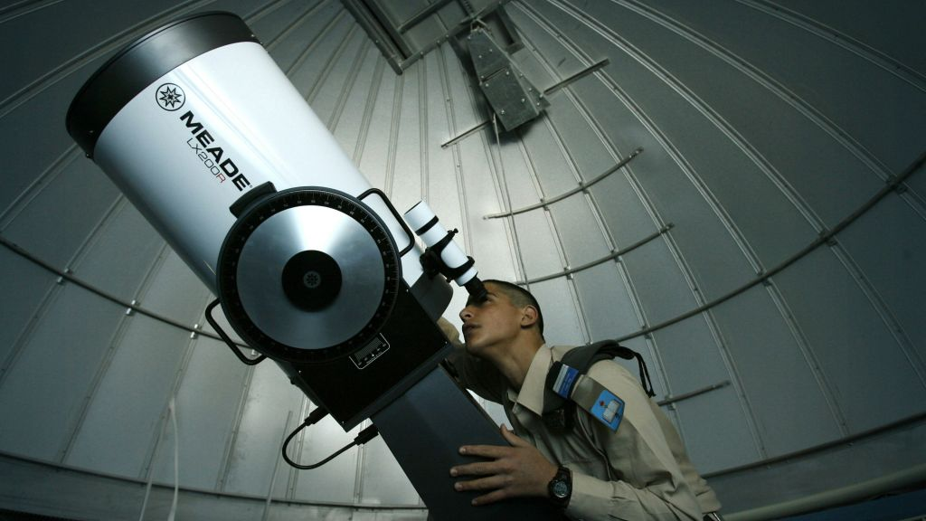 An illustrative photo of a student from an IDF air force school watching the stars through a telescope at a planetarium in Ma'ale Adumim, January 13, 2008. (Michal Fattal /FLASH90)