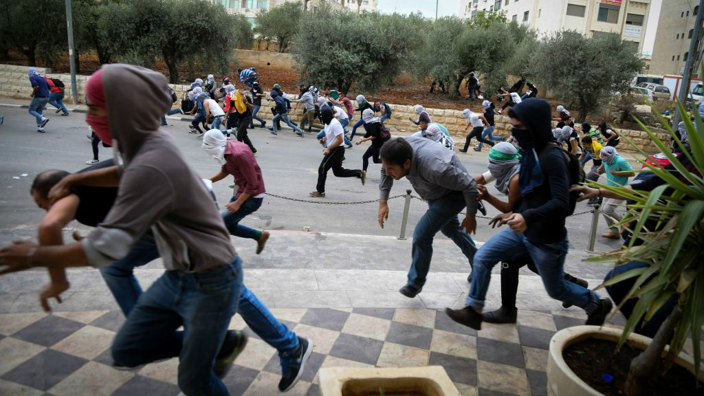 Palestinian protesters hurling stones at Israeli troops (not seen) during riots near the Jewish settlement of Bet El, near the West Bank city of Ramallah, October 10, 2015. (Flash90)