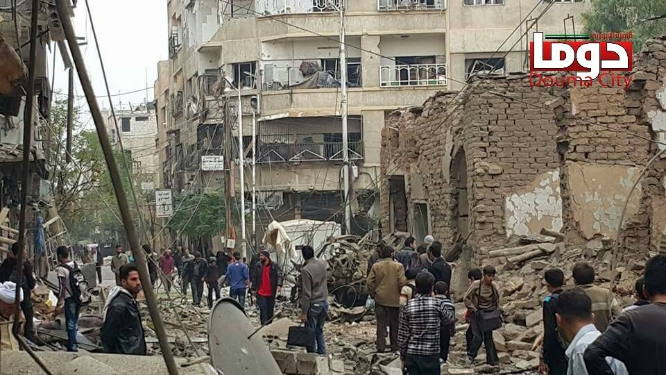 File. In this photo provided by the Syrian anti-government activist group Douma Revolution, people gather near damaged buildings in the aftermath of an airstrike that activists said was carried out by Russia, in Douma, Syria, Thursday, October 29, 2015. (Douma Revolution via AP)
