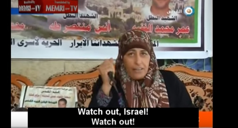 Mother of a slain Palestinian terrorist pulls out a knife and threatens -- during an interview on October 22, 2015 -- to carry out her own attack. (screen capture: YouTube)
