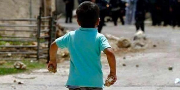 A young boy toddles toward Israeli soldiers, rock in hand. Via twitter.com