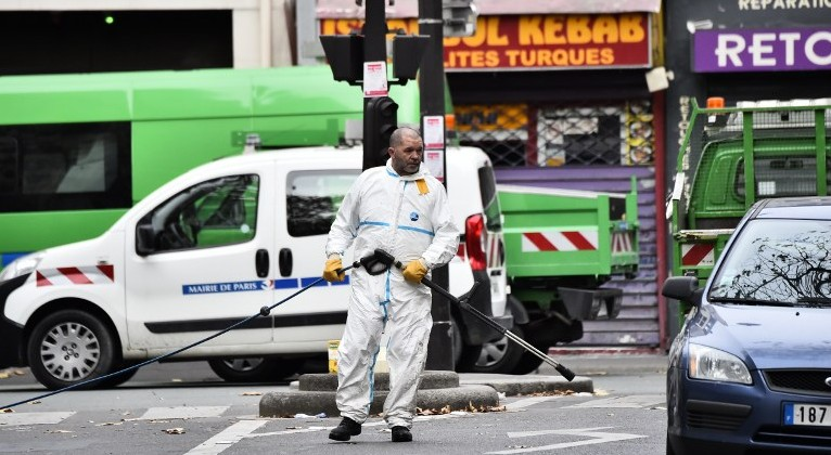A crime scene cleaner is pictured at the Rue de Charonne in Paris on November 14, 2015, following a series of coordinated attacks in and around Paris late Friday that left at least 127 people dead. (AFP PHOTO/LOIC VENANCE)