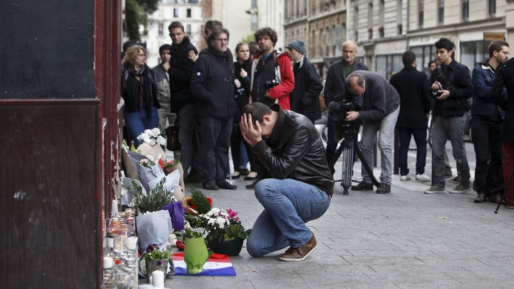 A man holds his head in his hands as he lays flowers in front of the Carillon cafe, in Paris, Saturday, Nov.14, 2015. (AP Photo/Thibault Camus)