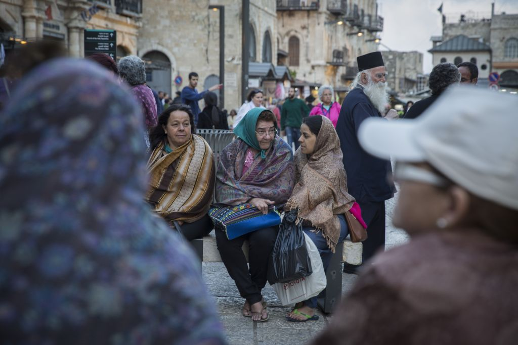 Tourists cover themselves in scarves as they wait for their group at Jaffa Gate in Jerusalem's Old City, as tempratures begin to drop and winter sets in, October 28, 2015. (Hadas Parush/Flash90)