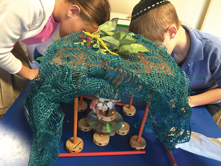 Students works on creating a model sukkah with recycled materials.