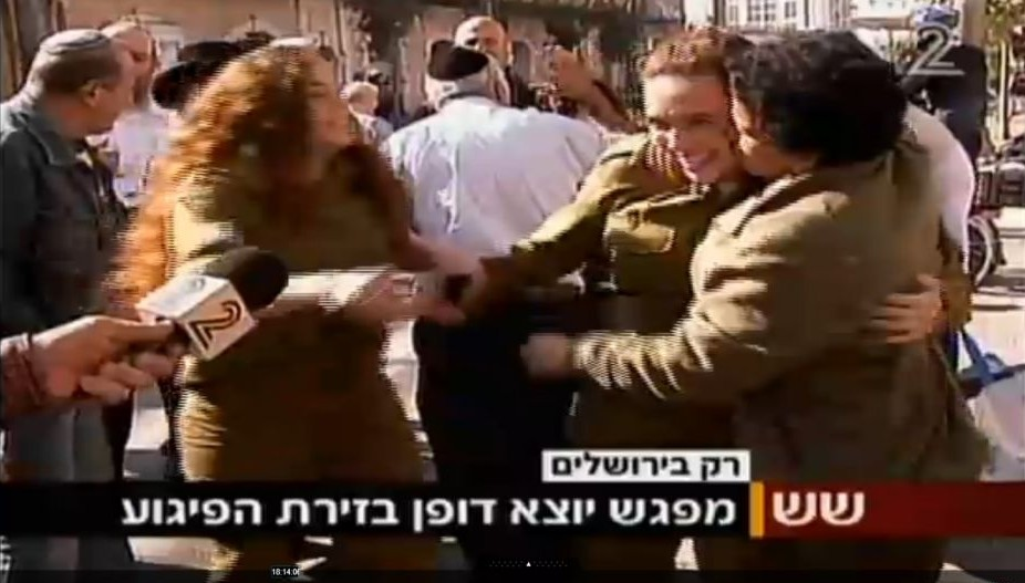Umm al Fahm woman Hawala Jaber (right) hugs and kisses a female IDF soldier a short time after a terror attack in Jerusalem on November 23 2015. Jaber was earlier interviewed by Channel 2 and criticized the recent wave of Palestinian terror attacks. (Screen capture Channel 2)