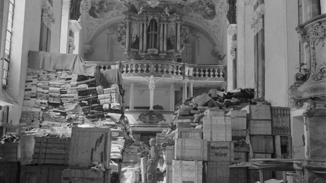 GI guarding looted art stored at Schlosskirche Ellingen, Bavaria (April 1945). Wikimedia Commons