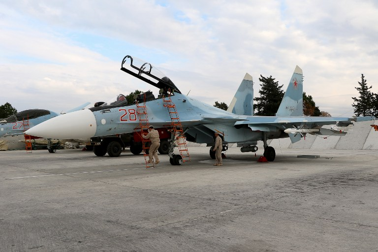 Russian servicemen prepare a Russian Sukhoi Su-30SM fighter jet before a departure for a mission at the Russian Hmeimim military base in Latakia province, in the northwest of Syria, on December 16, 2015. (AFP/Paul Gypteau)