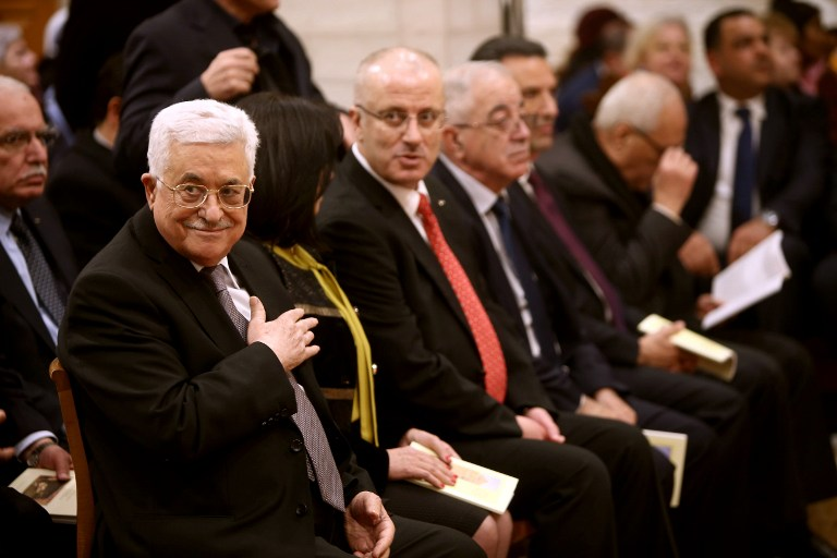 Palestinian Authority President Mahmoud Abbas (L) attends a Christmas Midnight Mass at the Church of the Nativity in the West Bank town of Bethlehem on December 25, 2015. (AFP PHOTO/ Fadi Arouri/ POOL / AFP / POOL / FADI AROURI)