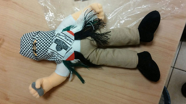 A doll wearing a kufiyah and holding a stone, part of a shipment of 4,000 such dolls intercepted by Haifa customs. They were meant to be sold in Palestinian markets. (Haifa customs)