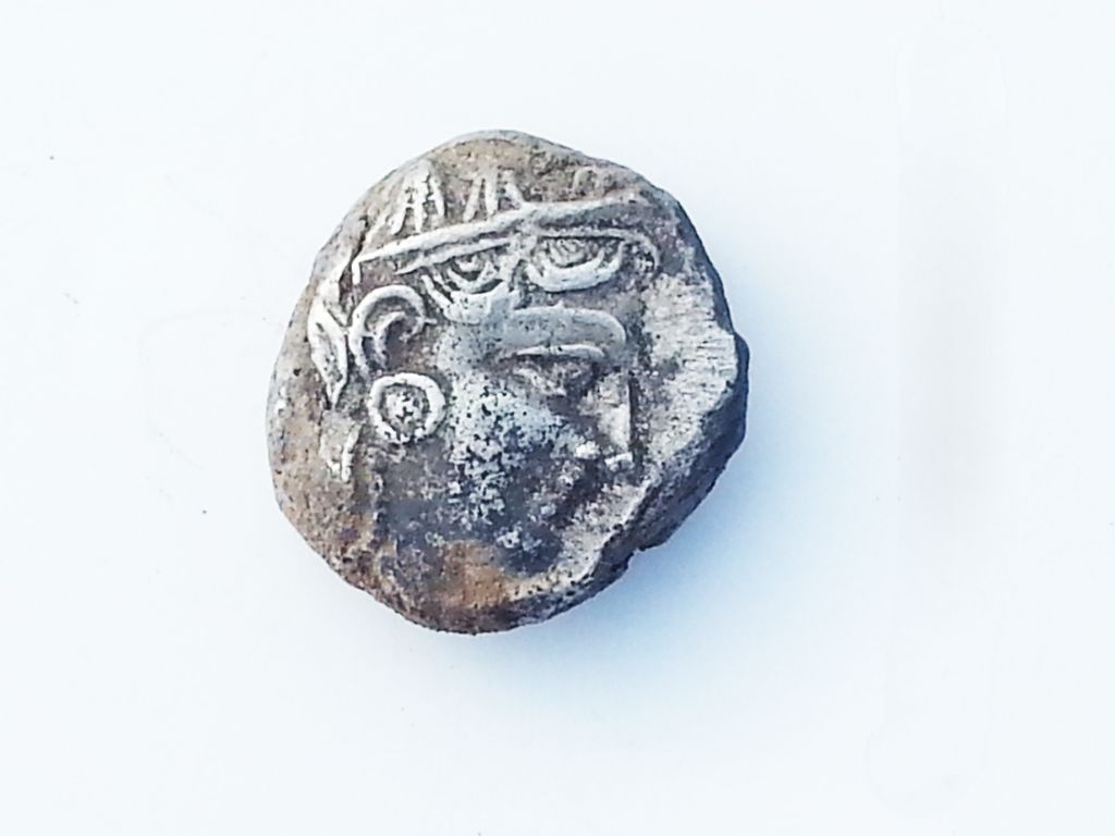 Obverse of a 4th century silver coin with the head of the goddess Athena found in a 2,700-year-old farmhouse near Rosh Ha'ayin. (Israel Antiquities Authority)