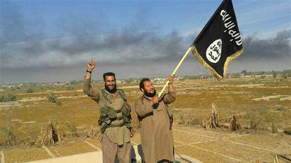 Illustrative photo of Islamic State militants, with an IS fighter waving the group flag in Fallujah, Iraq, west of Baghdad, June 28, 2015. (Militant website of IS, via AP)