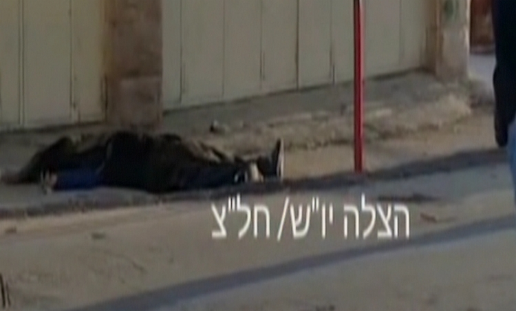 The covered body of an attacker lies on the ground after he was shot dead in a stabbing in the West Bank city of Hebron on December 7, 2015 that seriously wounded one person. (screen capture: Channel 10)