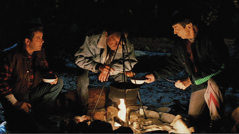 "As Captain Kirk, Shatner draws near the warmth of a campfire with Leonard Nimoy (Dr. Spock), and DeForest Kelly (Dr. McCoy) on earth between adventures in ""Star Trek V: The Final Frontier."""