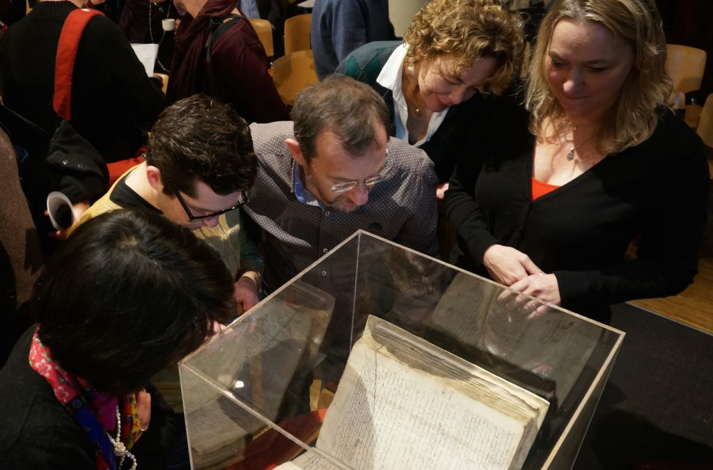 Attendees at an Amsterdam symposium on whether to lift the ancient order of excommunication against the philosopher Baruch Spinoza examining a copy of the original writ against him, December 6, 2015 (Cnaan Liphshiz/JTA)