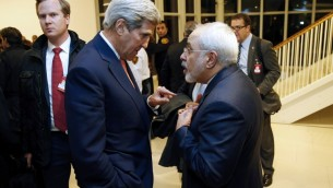 US Secretary of State John Kerry speaks with Iranian Foreign Minister Mohammad Javad Zarif after the UN atomic watchdog verifies that Iran has met all conditions of the July 2015 nuclear deal, in Vienna on January 16, 2016. (AFP/POOL/KEVIN LAMARQUE)