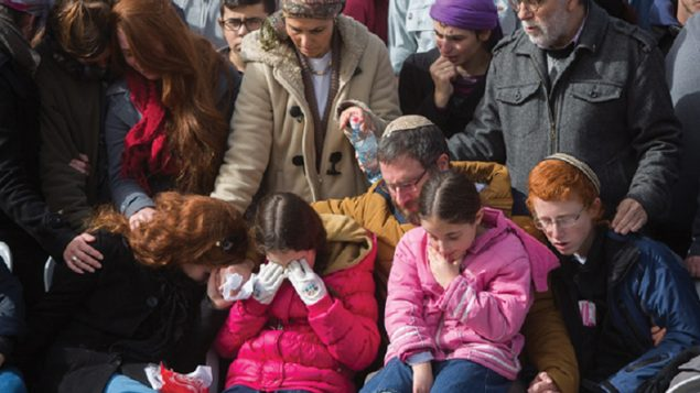 The husband and children of Dafna Meir grieving at her funeral in Jerusalem Tuesday, the day after her stabbing death.