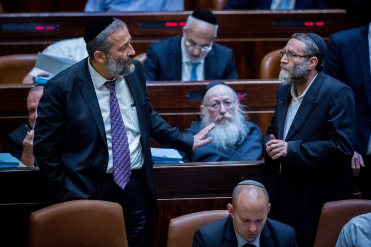 Shas party leader Aryeh Deri (L) speaks with Moshe Gafni of the United Torah Judaism party on September 2, 2015. (Yonatan Sindel/Flash90)