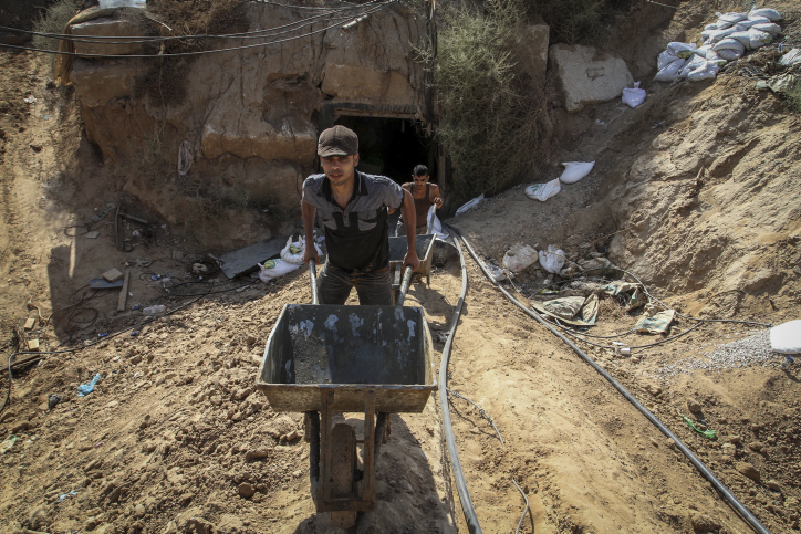 Palestinian men work at the entrance of a tunnel, used for smuggling supplies between Egypt and the Gaza Strip, after being flooded with seawater by Egyptian army, in Rafah in southern Gaza, on October 1, 2015. (Abed Rahim Khatib/ Flash90)