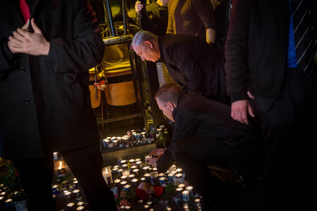 Prime Minister Benjamin Netanyahu lights a memorial candle at the Simta pub on Dizengoff Street in central Tel Aviv, on January 02, 2016, a day after two people were killed in a shooting there. Next to him is Public Security Minister Gilad Erdan (Miriam Alster/Flash90)