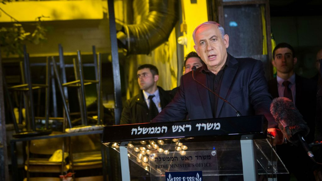 Prime Minister Benjamin Netanyahu speaks to press after lighting a candle outside a pub on Dizengoff Street in central Tel Aviv, January 02, 2016, a day after two people were killed in a shooting at the bar. (Miriam Alster/Flash90)