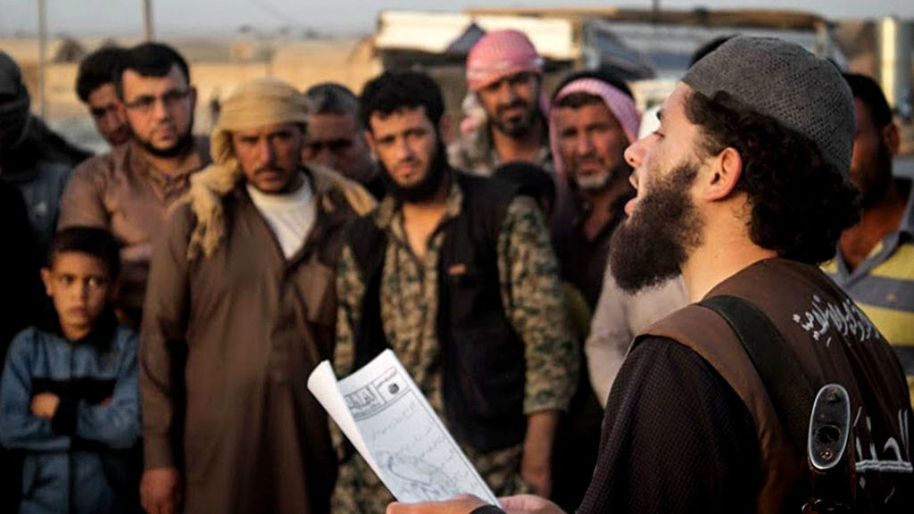 "In this file photo released on May 14, 2015, by a militant website, a member of the Islamic State group's vice police known as ""Hisba"" reads a verdict handed down by an Islamic court in Raqqa, Syria, sentencing many they accused of adultery to lashing. A Hisba member ""must be gentle and pleasant toward those he orders or reprimands,"" says an IS document obtained by the AP. Yet, escaped Syrians complain of the cruelty of the Hisba. (Militant website via AP, File)"